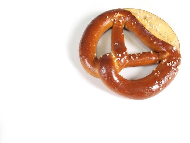 Brown salted pretzel against white background