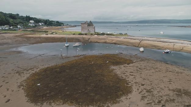 海辺の古い歴史的な城の遺跡で海湾空中飛ぶ鳥の茶色の砂のビーチ