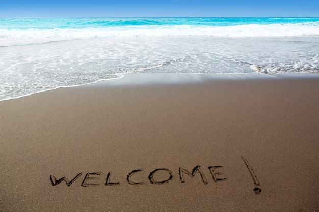 Brown sand beach with written word welcome