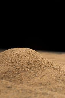 Brown sand on black wall