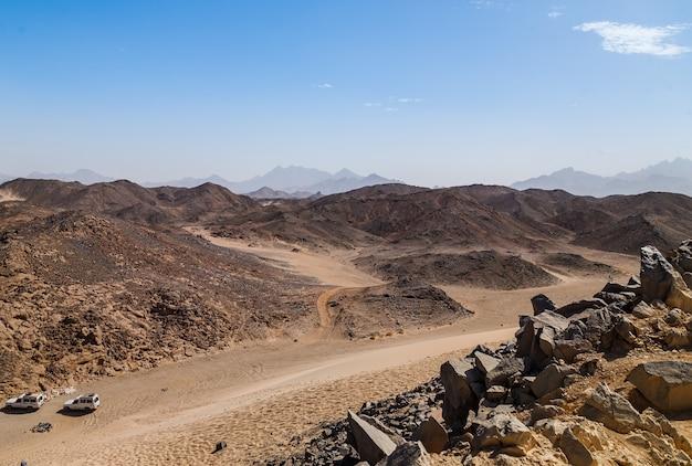 Коричневый песок, пустынные дюны и холмы на голубом небе