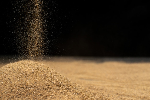 Brown sand falling on black wall