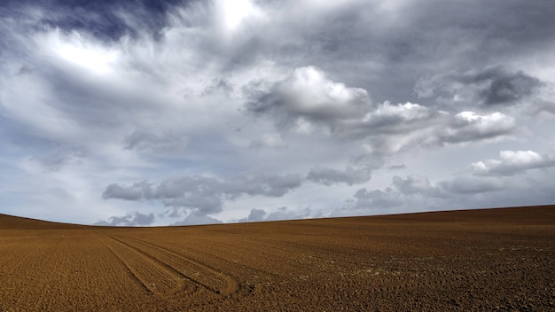Brown sandy land under the dark cloudy grey sky