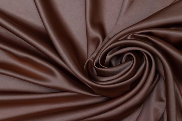 茶色のサテン、絹のような生地、波、カーテン。美しい繊維の背景。