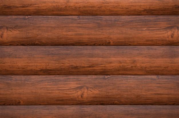 집 벽에있는 갈색 사이딩은 나무 통나무를 모방했습니다.