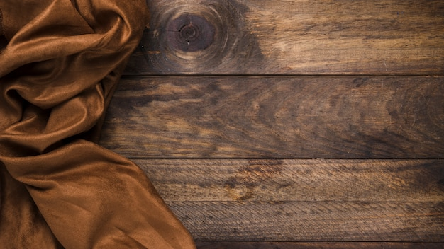 Brown silk textile on weathered wooden table