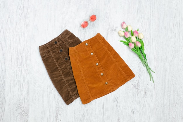 Brown skirt with buttons, pink sunglaasses and bouquet of tulips. fashionable concept