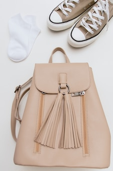 Коричневые кроссовки, бежевый рюкзак, белые носки на бежевой стенке