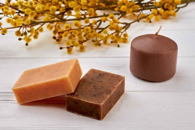 Коричневые брусочки спа-мыла и свеча с вербой