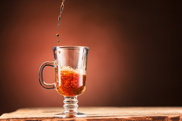 Brown splashes out drink from cup of tea on a brown wall