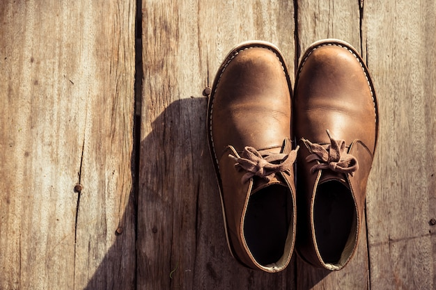 Brown stylish boots on wood background,  retro color