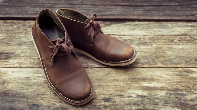 Brown stylish boots on wood ,  retro color
