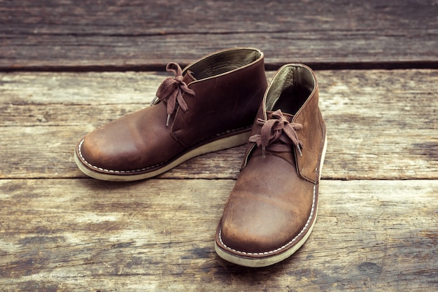 Brown stylish boots on wood, retro color