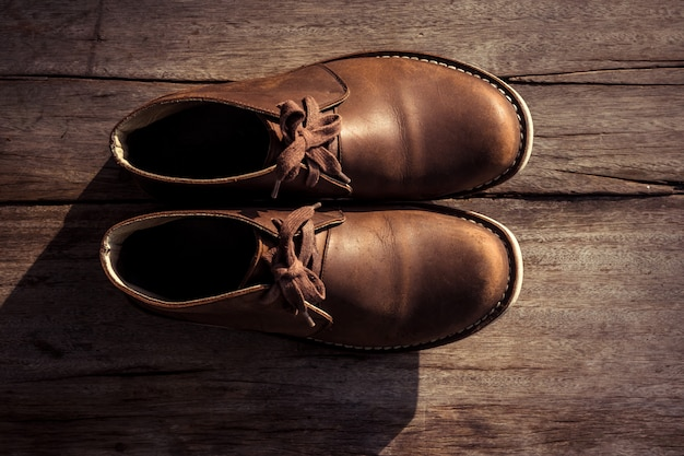 Brown stylish boots on wood