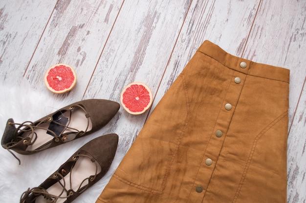 茶色のスエードのスカート、茶色のスエードの靴、グレープフルーツの半分をカット。木製。ファッションのコンセプトです。上面図