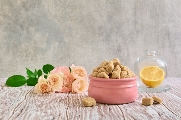 Brown sugar in a ceramic bowl, roses and lemon on wooden table