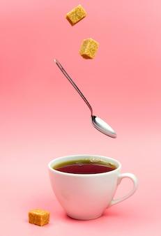 ブラウンシュガーキューブと紅茶のカップに落ちるスプーン。