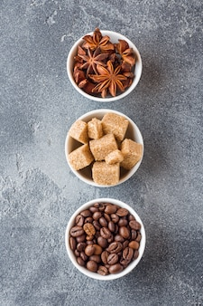 Brown sugar cubes, coffee beans and star anise on concrete background.