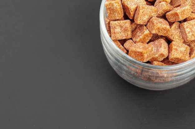 Brown sugar cubes on gray background