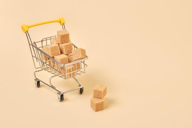 Кубики коричневого сахара в миниатюрной тележке для покупок на бежевой поверхности