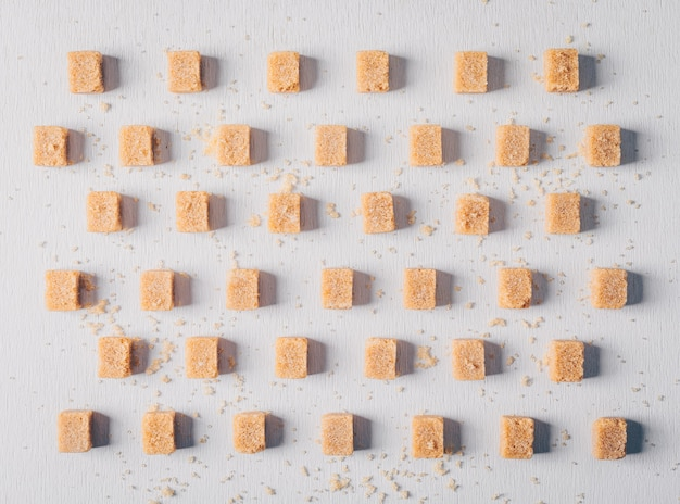 Brown sugar cubes lined up. flat lay.