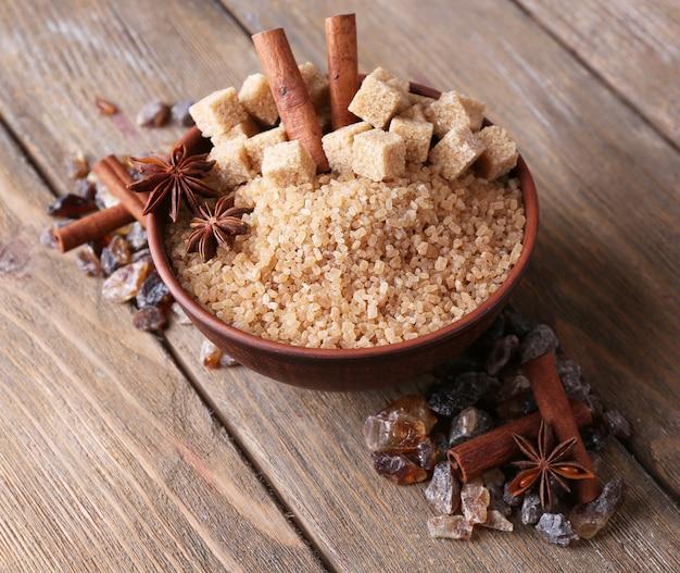 Кубики коричневого сахара, тростник и кристаллический сахар в миске на деревянном столе