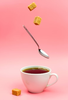 Brown sugar cubes and a spoon falling into the cup of black tea.