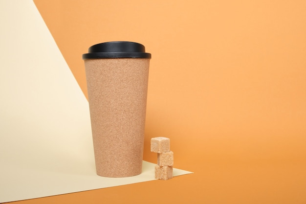 Brown sugar cubes and thermo mug made of cork on a beige and brown background copy space