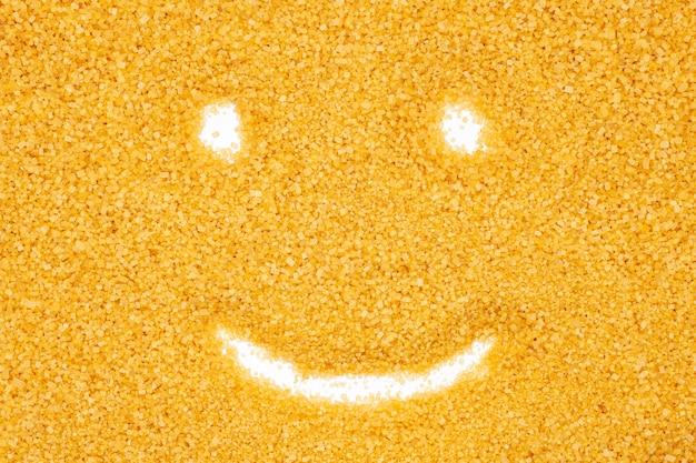 Brown sugar, funny smile face, close up, macro, top view.