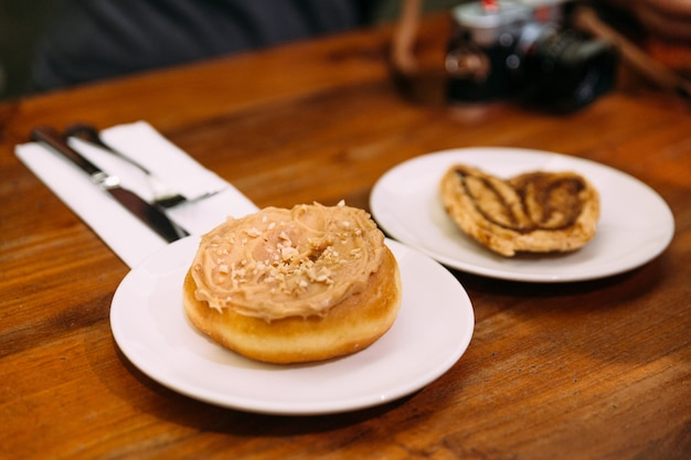 Brown sugar glazed apple cinnamon baked donuts in white plate on wooden table.