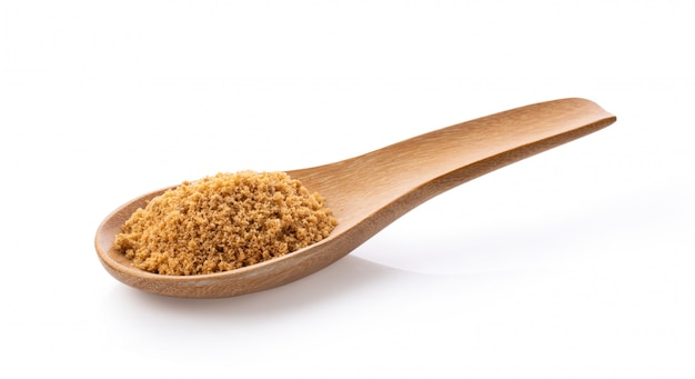 Brown sugar in wood spoon isolated on white background