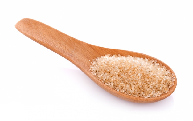 Brown sugar in wooden spoon on white background