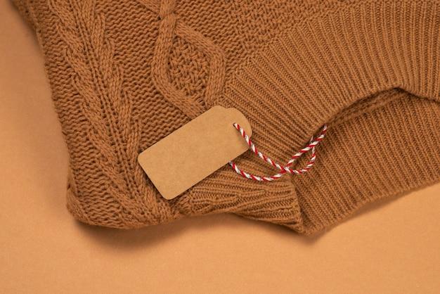 Коричневая бирка на коричневом вязаном свитере