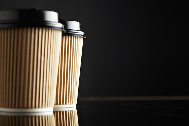 Brown take away paper cups closed with caps isolated on left
