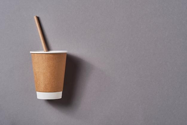 Коричневая кофейная кружка на вынос с бумажной питьевой соломкой на серой таблице цветов тенденции. нулевые отходы, концепция устойчивого образа жизни. вид сверху с копией пространства