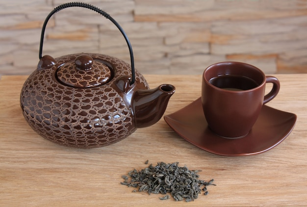 Brown teapot and cup with green tea against a stone wall