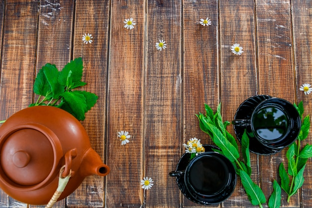 新鮮なミントとカモミールのテーブルと木製のお茶の2つの黒いカップの近くの茶色のティーポット。お茶 。フレーム、copyspace。上面図。