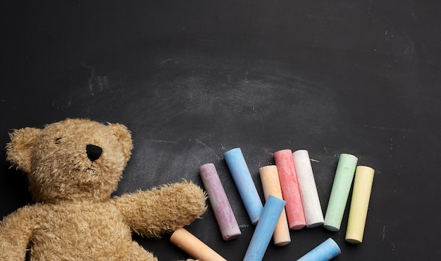茶色のテディベアと学校に戻って黒いチョークボードにカラフルなクレヨン
