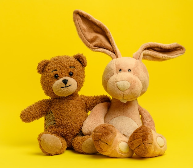 Brown teddy bear and cute rabbit sit on a yellow wall, toy with patches