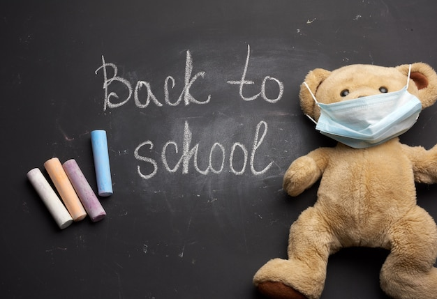 Brown teddy bear in a disposable medical mask on a black chalkboard background