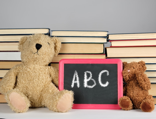 Brown teddy bear and empty black board in red frame on the   of pile of books
