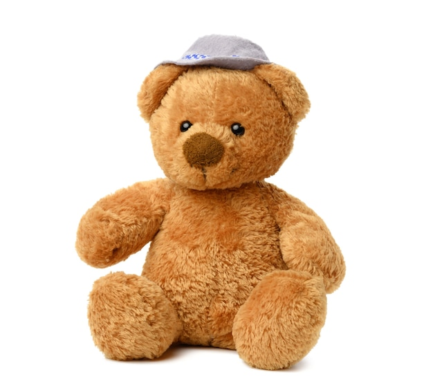 Brown teddy bear in a felt hat sits on a white isolated surface, cute baby toy