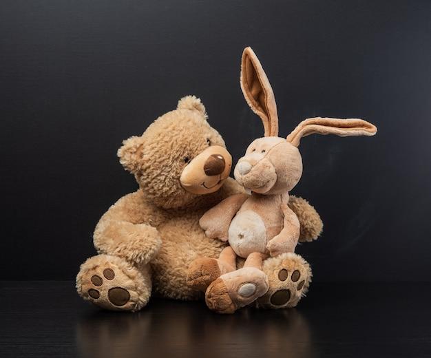 검은 분필 보드 배경에 그의 무릎에 테디 토끼를 들고 갈색 곰