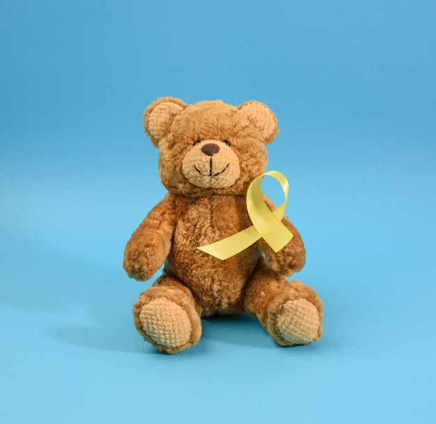 Brown teddy bear holds in his paw a yellow ribbon folded in a loop on a blue background. concept of the fight against childhood cancer.