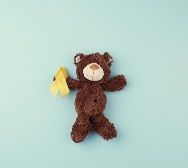 Brown teddy bear holds in his paw a yellow ribbon folded