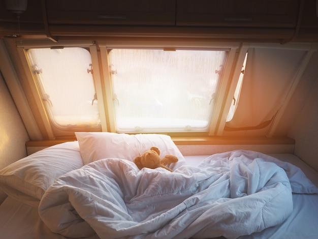 Коричневый плюшевый мишка на кровати в спальне передвижного автомобиля утром.