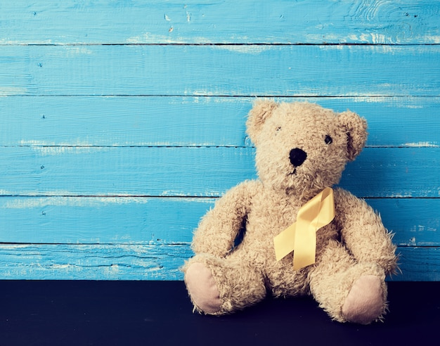 Brown teddy bear sits on a blue surface