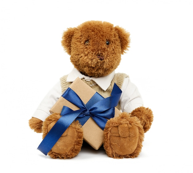 Brown teddy bear sits holds a box wrapped in brown kraft paper