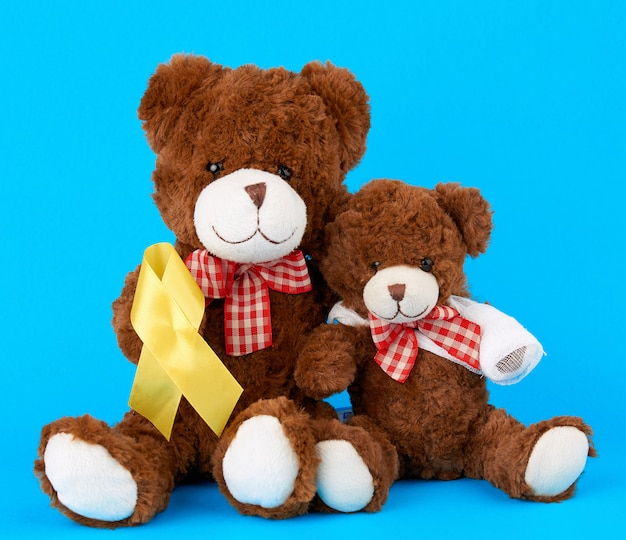 Brown teddy bear sits and holds in his paw a yellow silk ribbon on blue
