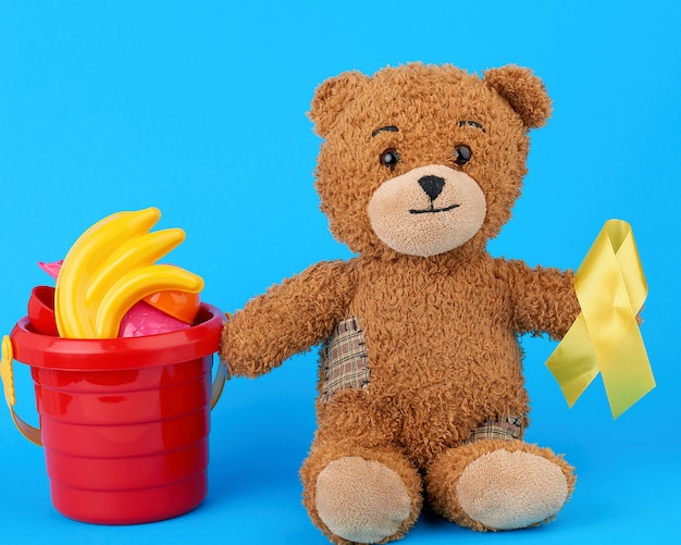 Brown teddy bear sits and holds in his paw a yellow silk ribbon